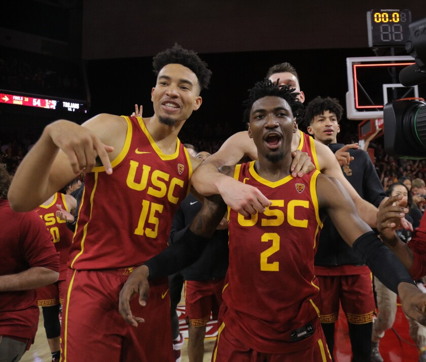 Jonah Mathews (2) is swarmed by Isaiah Mobley (15) and other USC teammates after his game-winning three-pointer March 7, 2020.
