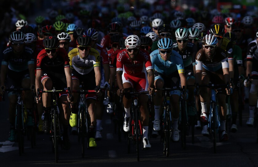 FILE - In this Sept. 16, 2018 file photo, cyclists pedal during the final leg of the Spanish Vuelta cycling race in Madrid, Spain. The Spanish Vuelta starts Tuesday Oct. 20, 2020 amid tight health restrictions in the hopes of avoiding the coronavirus infections that have knocked some riders out of the Giro d'Italia. (AP Photo/Manu Fernandez, File)