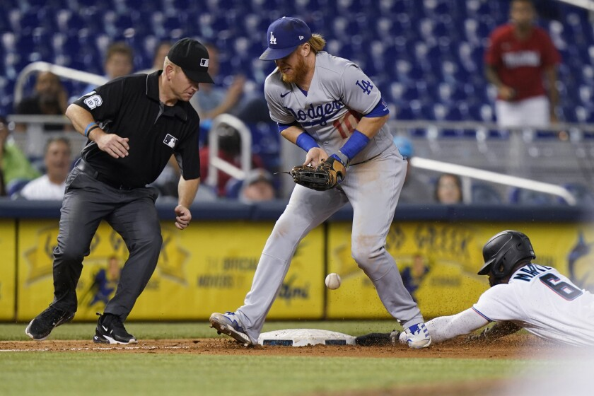 Miami's Starling Marte slides into third base as the Dodgers' Justin Turner is unable to hang on to the throw.