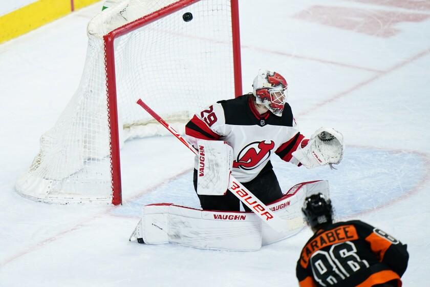 New Jersey Devils' Mackenzie Blackwood, left, cannot stop a goal by Philadelphia Flyers' Joel Farabee during the third period of an NHL hockey game, Saturday, May 1, 2021, in Philadelphia. (AP Photo/Matt Slocum)
