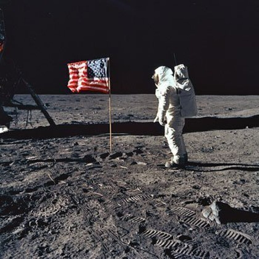 Apollo 11 astronaut Buzz Aldrin with American flag. Skeptics say the scene is faked — that without an atmosphere, a flag couldn't wave. The flag isn't. It's suspended by a cross-bar and simply wrinkled. (NASA)