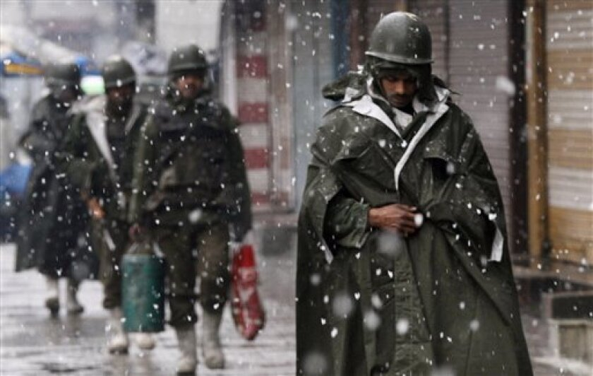 Paramilitary soldiers walk past closed shops as it snows in central Srinagar, India, Saturday, Feb. 6, 2010. Fresh protests erupted fueled by the death of the second teenager on Friday, as thousands of soldiers in riot gear patrolled the streets in Indian Kashmir's main city for the third straight day to quell protests. (AP Photo/ Dar Yasin)