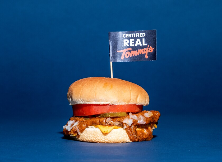 "A chili burger with a little sign on a toothpick that says ""Certified Real Tommy's."""