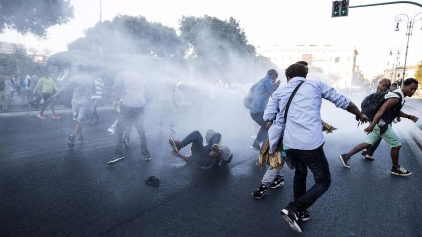 Italian law enforcement officers use a water cannon to disperse migrants in central Rome on Thursday