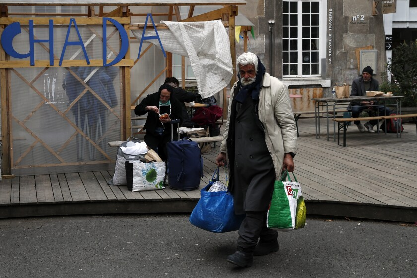Homeless people arrive in the 'Aurore' center for homeless and migrants in Paris, Thursday, April 2, 2020. The United Nation's independent expert on poverty is warning that the worst impacts from the coronavirus pandemic on poverty are yet to come, and that measures taken by governments to protect societies are insufficient. (AP Photo/Francois Mori)