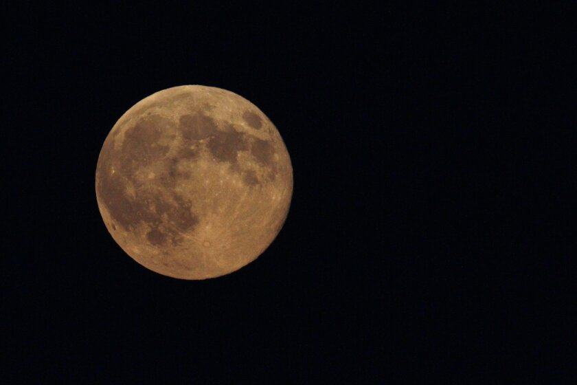 The supermoon appears yellow as the sky darkens over Edgartown, Mass., Sunday, Aug. 10, 2014, on the island of Martha's Vineyard. President Barack Obama and his family are vacationing on the island. (AP Photo/Jacquelyn Martin)