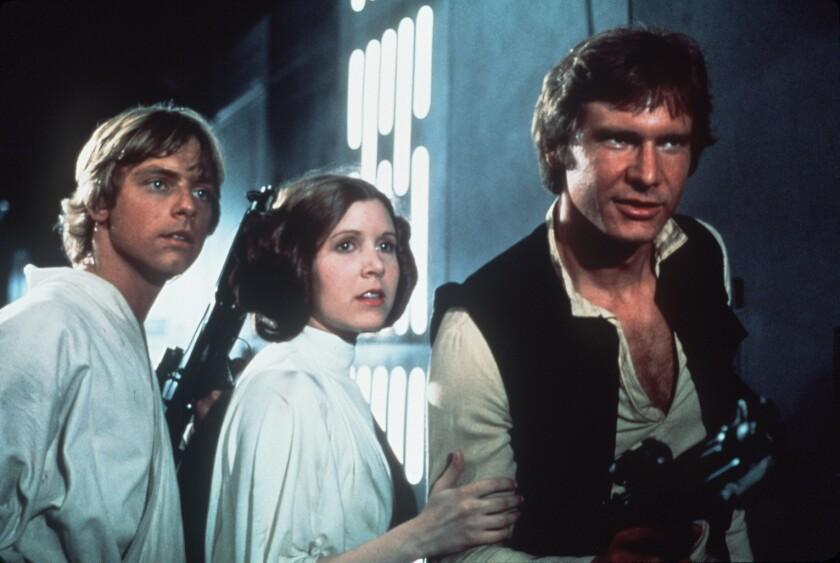 """Carrie Fisher, al medio, en una escena de """"Star Wars"""" (1977), rodeada de Mark Hamill -a la izquierda- y Harrison Ford -a la derecha-. La actriz dejó de existir tras sufrir un infarto durante un vuelo de avión."""