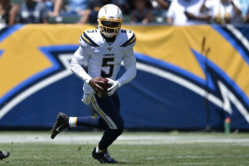 Chargers quarterback Tyrod Taylor runs with the ball.