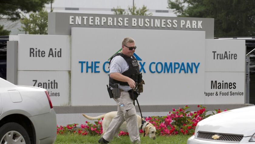 ATF police officer with a sniffing dog walks out the industrial complex in Harford County, Md., Thur