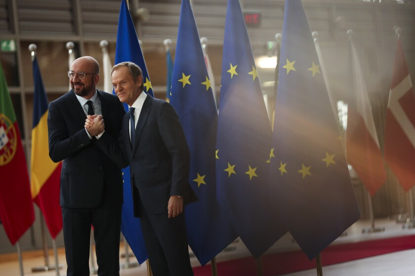 Outgoing European Council President Donald Tusk, right, shakes hands with New European Council President Charles Michel at the European Council headquarters in Brussels, Friday, Nov. 29, 2019. (AP Photo/Francisco Seco)