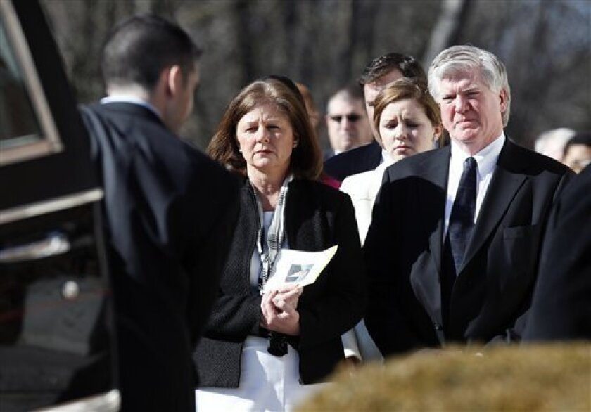 President and general manager of the Toronto Maple Leafs Brian Burke, right, and his first wife Kerry, left, watch as the casket of their son Brendan is taken from the hearse into a memorial service in Canton, Mass., Tuesday, Feb. 9, 2010. (AP Photo/Michael Dwyer)