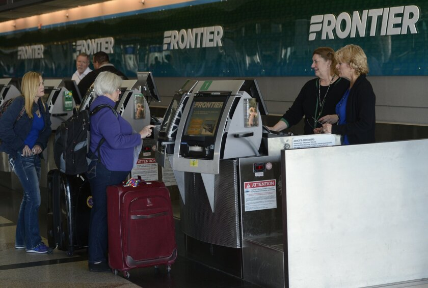 Frontier Airlines customer service agents help customers at the ticket counter at Denver International Jan. 16, 2015.
