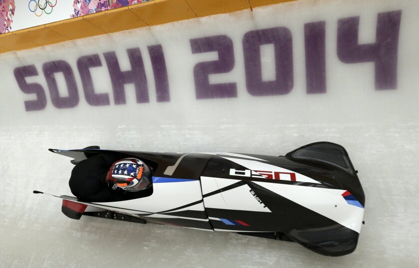 The USA-2 sled from the United States piloted by Nick Cunningham, takes a turn during a training run for the two-man bobsled at the 2014 Winter Olympics, Thursday, Feb. 6, 2014, in Krasnaya Polyana, Russia. (AP Photo/Michael Sohn)