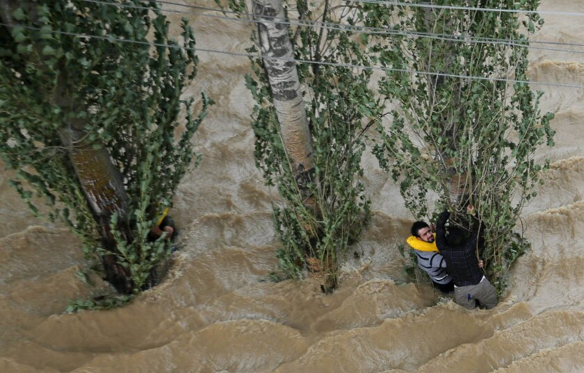 Kashmiris hang on to a tree to prevent being swept away by floodwaters in Srinagar, India, Tuesday, Sept. 9, 2014. The death toll from floods in Pakistan and India reached 400 on Tuesday and have put more than half a million people in peril and rendered thousands homeless in the two neighboring sta