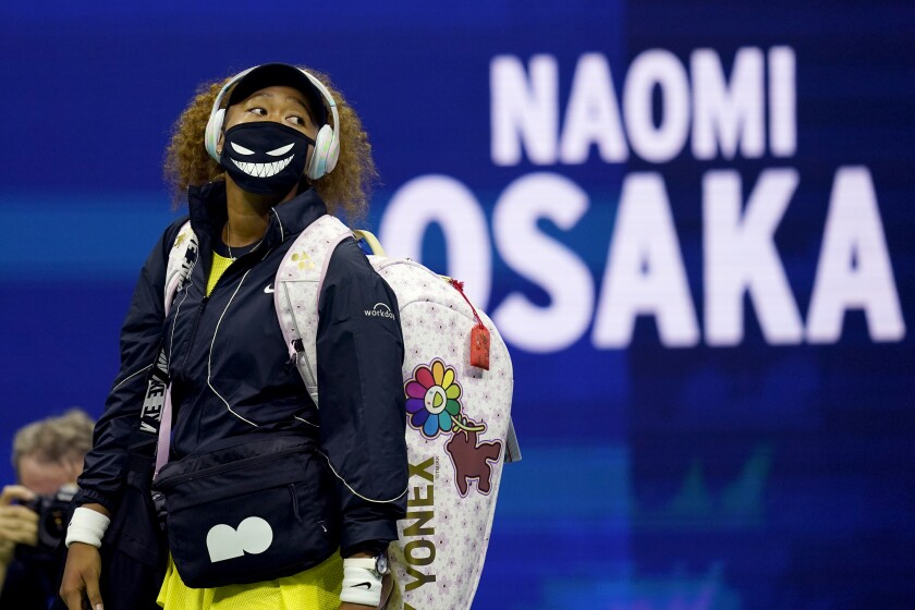 Naomi Osaka walks onto the court for her first-round U.S. Open match against Marie Bouzkova on Monday in New York.