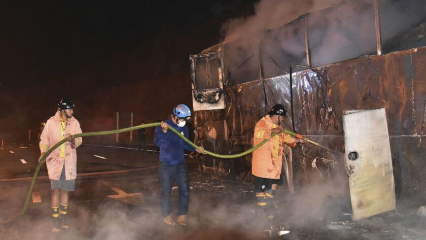 Firefighters douse flames after a fire aboard a double-decker bus killed 20 people in Thailand's Tak province on March 30.