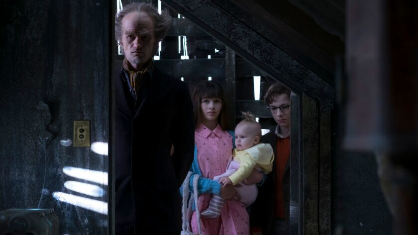 """The evil Count Olaf (Neil Patrick Harris) shows the Baudelaire orphans (Malina Weissman, Presley Smith, Louis Hynes) to their new quarters in Netflix's """"Lemony Snicket's A Series of Unfortunate Events."""""""