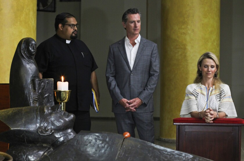California Gov. Gavin Newsom and his wife, Jennifer Siebel Newsom, visit the tomb of Archbishop Osca