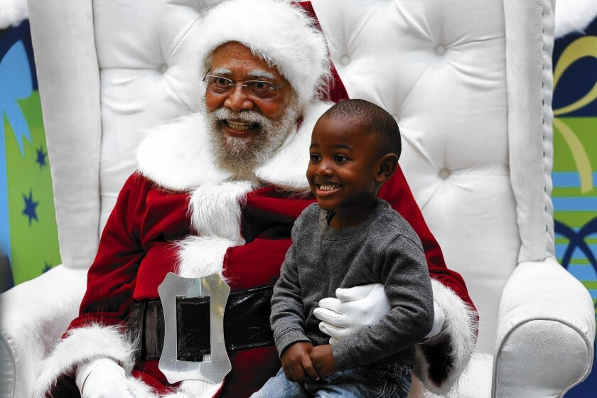 Jahleel Logan, 3, poses with Santa Claus, a.k.a. Langston Patterson, 77
