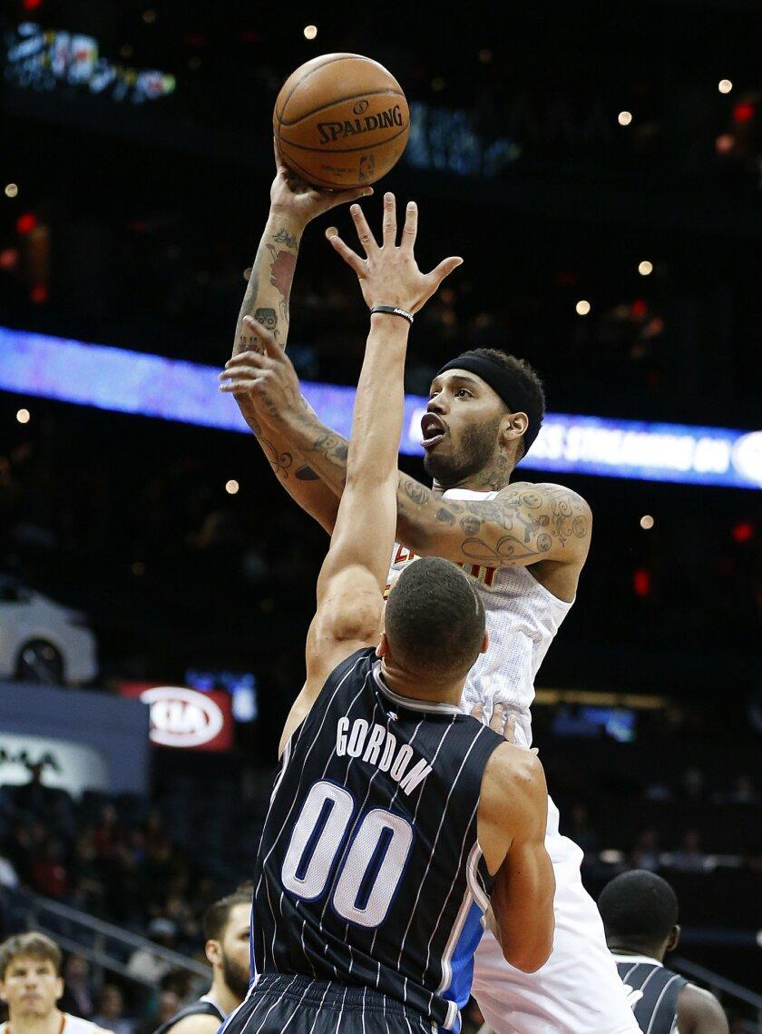 Atlanta Hawks forward Mike Scott (32) shoots as Orlando Magic forward Aaron Gordon (00) defends in the first half of an NBA basketball game Monday, Feb. 8, 2016, in Atlanta. (AP Photo/John Bazemore)