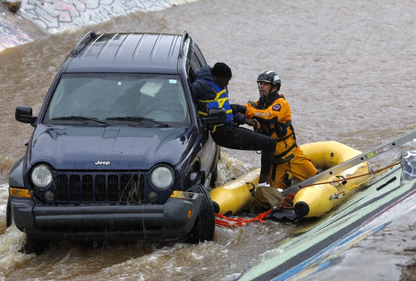 A member of San Diego Fire Rescue pulled one of the two occupants from a Jeep trapped in Chollas Creek after the vehicle veered off of Highway 94 at Interstate 15.