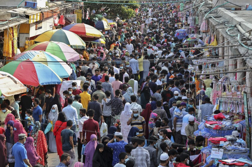 Shoppers crowd at a marketplace in Dhaka, Bangladesh, Friday, May 7, 2021. India's surge in coronavirus cases is having a dangerous effect on neighboring Bangladesh. Health experts warn of imminent vaccine shortages just as the country should be stepping up its vaccination drive, and as more contagious virus variants are beginning to be detected. (AP Photo/Mahmud Hossain Opu)