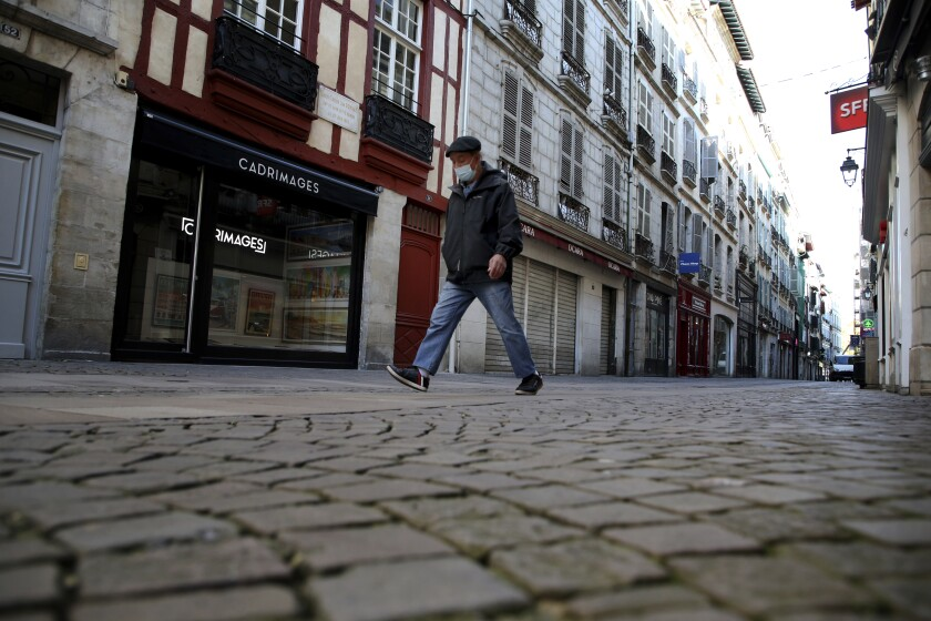 A man walks in an empty street during a nationwide confinement to counter the Covid-19, in Bayonne, southwestern France Friday, Oct. 30, 2020 . France re-imposed a monthlong nationwide lockdown Friday aimed at slowing the spread of the virus, closing all non-essential business and forbidding people from going beyond one kilometer from their homes except to go to school or a few other essential reasons. (AP Photo/Bob Edme)