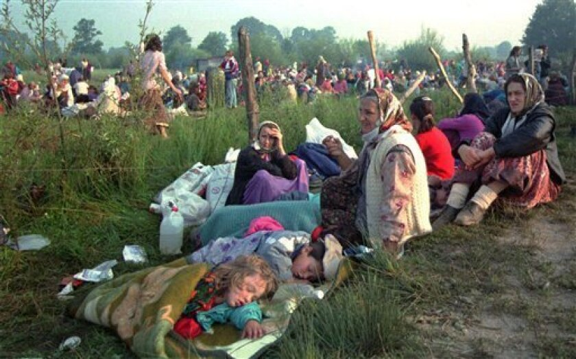 FILE -- In this July 14, 1995 file photo, refugees from the overrun U.N. safe haven enclave of Srebrenica who had spent the night outdoors, gather outside the U.N. base at Tuzla airport. Israeli police have arrested a former Bosnian Serb soldier suspected of playing a role in the 1995 massacre of B
