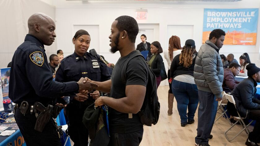 Tevin Green, center, shakes hands with New York Police Department recruiter Officer Omisanya during a job fair on Nov. 15, 2016, in Brooklyn.
