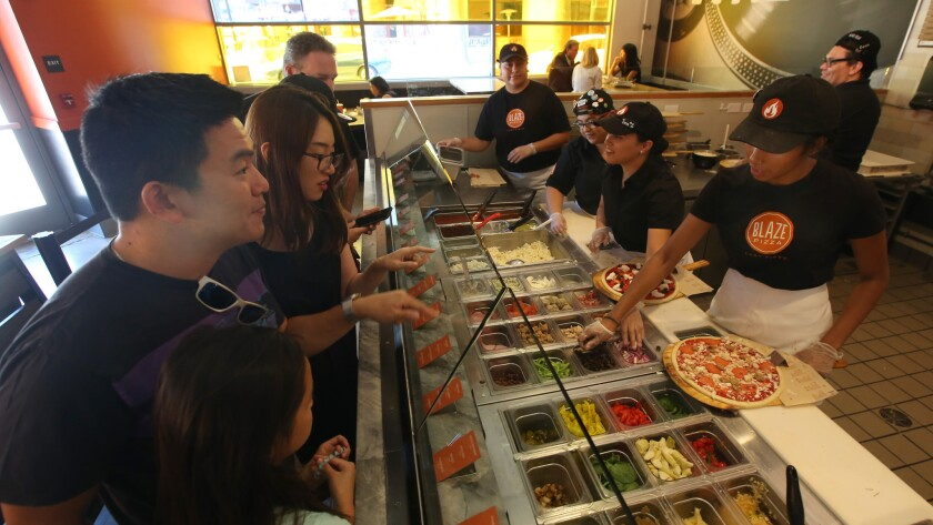 Customers watch as their pizza is being prepared as customers watch at Blaze Pizza in Pasadena on July 19. Blaze Pizza is a fast-casual pizza chain with national ambitions.