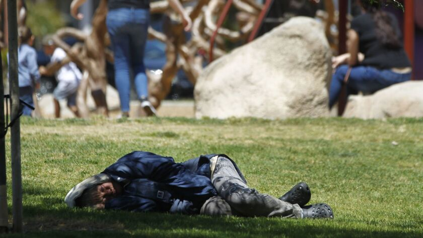 ESCONDIDO, May 3, 2018 | A woman sleeps on the grass as parents watch their children play on a playg