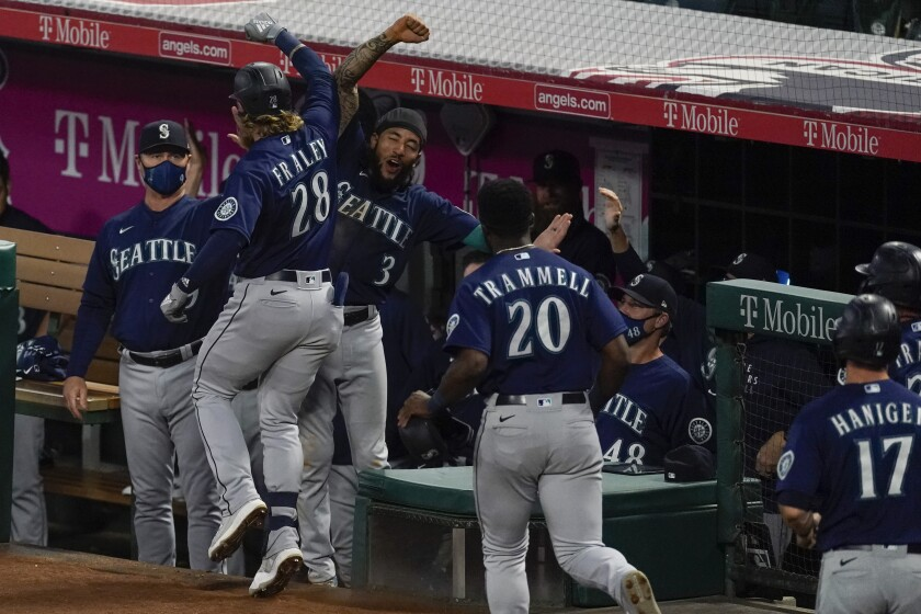 Seattle Mariners designated hitter Jake Fraley (28) celebrates with J.P. Crawford (3) after hitting a grand slam home run during the fourth inning of a baseball game against the Los Angeles Angels Saturday, June 5, 2021, in Anaheim, Calif. Mitch Haniger, Ty France, and Taylor Trammell also scored. (AP Photo/Ashley Landis)