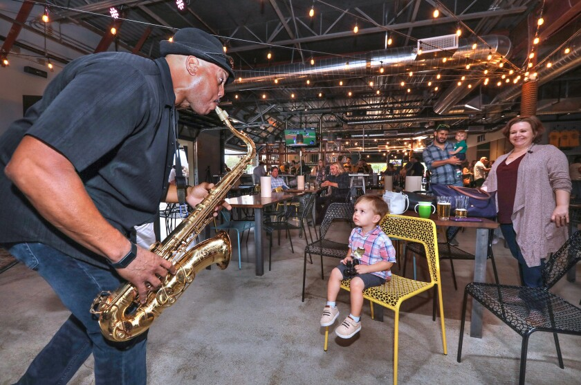 At a private preview party at My Yard Live on Saturday, saxophonist/singer Jerome Dawson, leader of jazz band Wazabe Blue, performs for 2-year-old Dylan Heffley, who was there with family members.