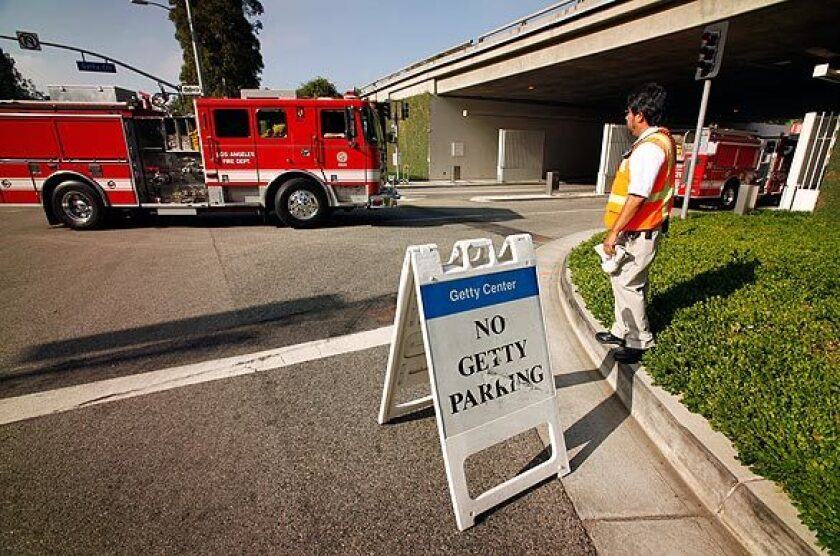 Getty Center employee Mario Cabrera monitors the center's main entrance on Sepulveda Boulevard, which was open only to firefighters.