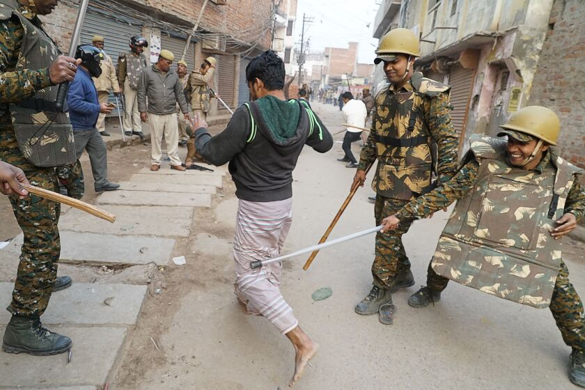 Indian police personnel clash with a protester during a demonstration against India's new citizenship law in Varanasi on Dec. 20.