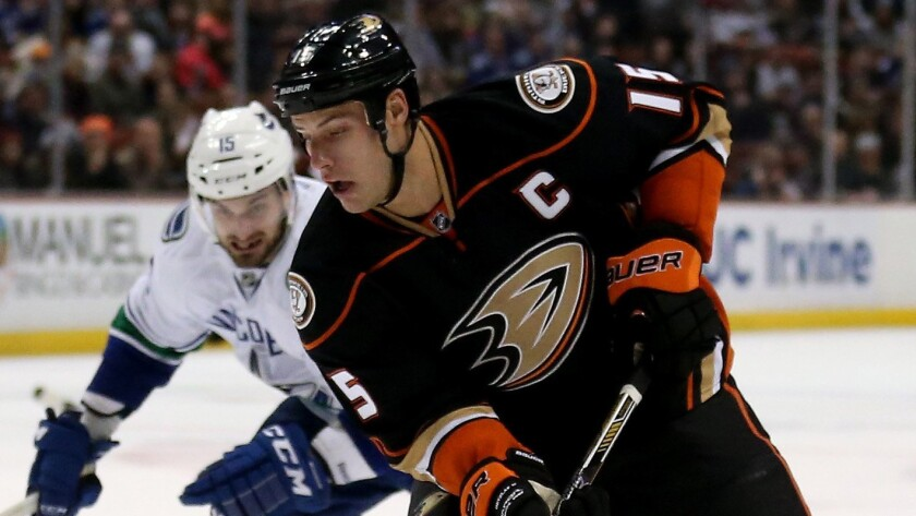 Ducks captain Ryan Getzlaf controls the puck in front of Vancouver Canucks forward Brad Richardson during a Ducks' win on Sunday.