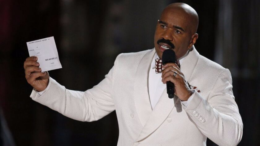 Steve Harvey holds up the card showing the winners after incorrectly announcing Miss Colombia as the