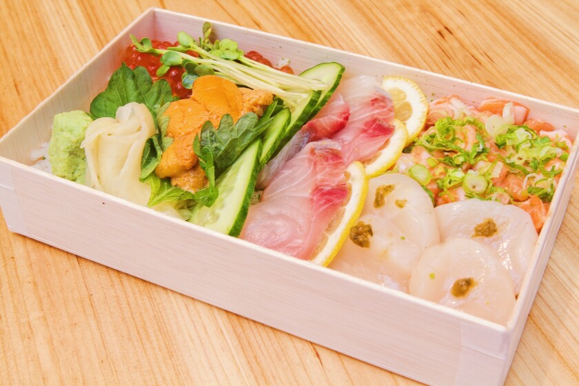 Raw fish and vegetables in a white box prepared by Yojimbo.