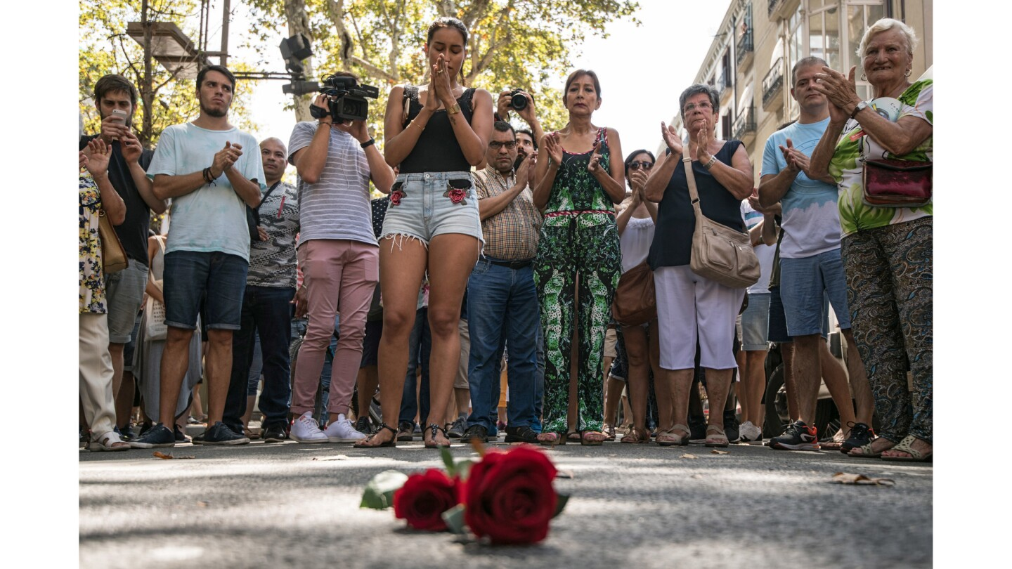 People gather around roses laid on the ground on Las Ramblas after one minute's silence for the victims of Thursday's terrorist attack in Barcelona, Spain.