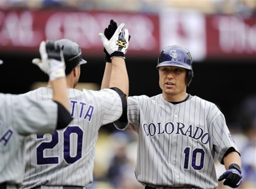 Colorado Rockies Jeff Baker, right, is congratulated by Chris Iannetta, center, and Omar Quintanilla after hitting a two-run home run against Los Angeles Dodgers during the second inning of the baseball game at Dodger Stadium in Los Angeles, Wednesday June 4, 2008. Iannetta scored on Baker's home run. (AP Photo/Kevork Djansezian)