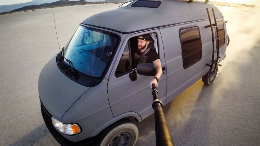 Nature photographer Travis Burke, 31, and Betty the Grey Wolf, the van he's used over the past four years to travel throughout North America. The Oceanside native held a contest this summer to give Betty away. The winner was Alaska's Wool Sock Project for the homeless.