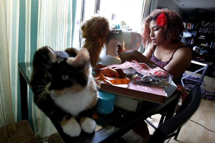 Jonaya Kemper, a member of the millennial generation, makes a scarf for a friend in Los Angeles' Thai Town while her cat chills out nearby. A new Pew surveys says millennials are more upbeat than others about their finances and the nation's future but are cool to many traditions, such as political parties and religious affiliations.