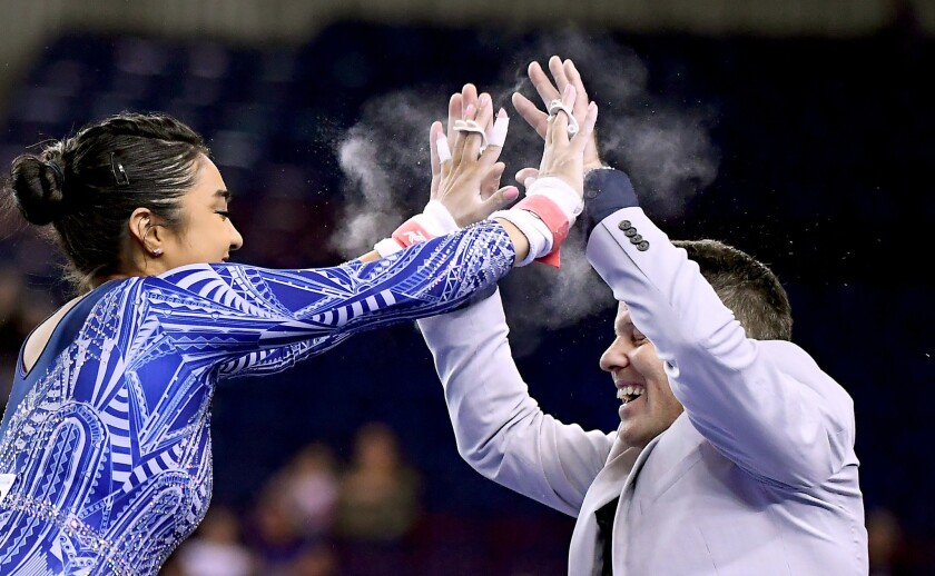 Felicia Hano celebrates with assistant coach Chris Waller after competing on the parallel bars at the NCAA gymnastics semifinals in Texas last year.