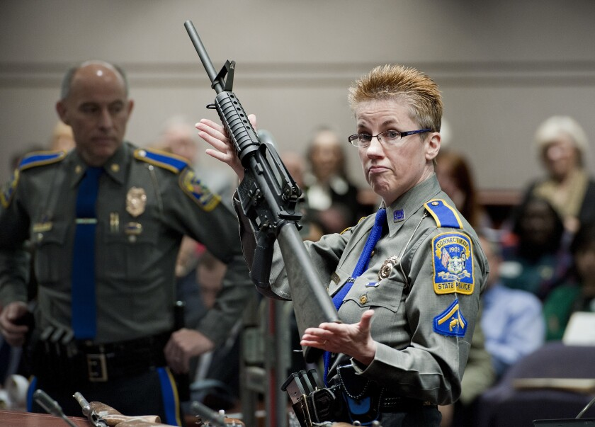 FILE - In this Jan. 28, 2013, file photo, firearms training unit Detective Barbara J. Mattson, of the Connecticut State Police, holds up a Bushmaster AR-15 rifle, the same make and model of gun used by Adam Lanza in the Sandy Hook School shooting, for a demonstration during a hearing of a legislative subcommittee reviewing gun laws, at the Legislative Office Building in Hartford, Conn. The Supreme Court said Tuesday, Nov. 12, 2019, a survivor and relatives of victims of the Sandy Hook Elementary School shooting can pursue their lawsuit against the maker of the rifle used to kill 26 people. (AP Photo/Jessica Hill, File)