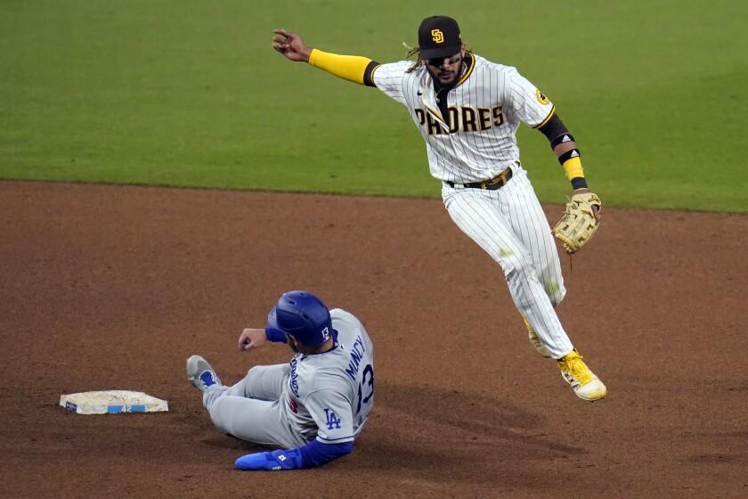 El campocorto de los Padres de San Diego Fernando Tatis Jr. (derecha) salta sobre Max Muncy