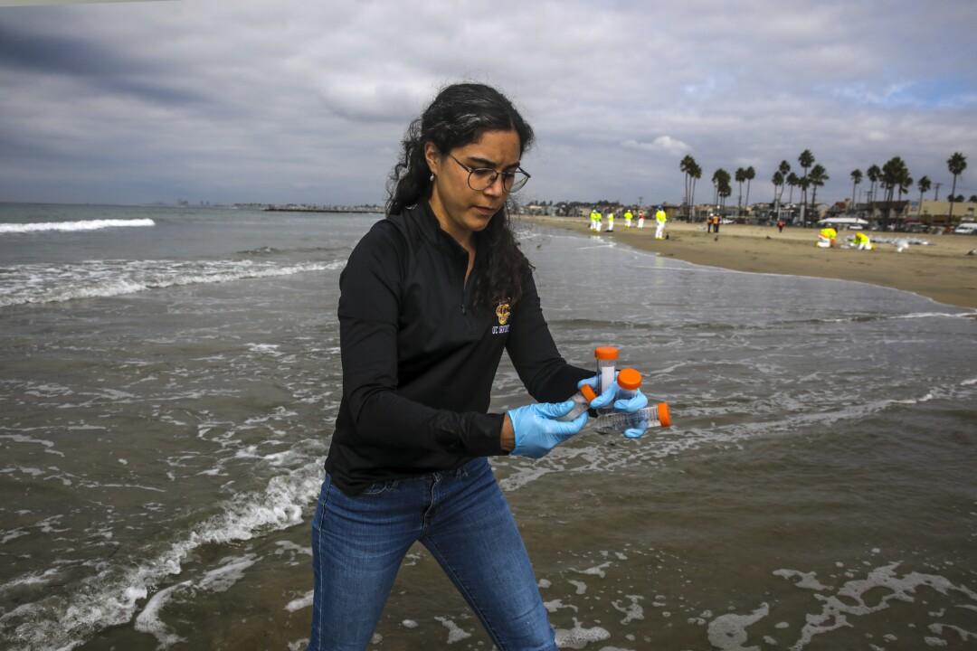 A woman on a beach holds plastic vials