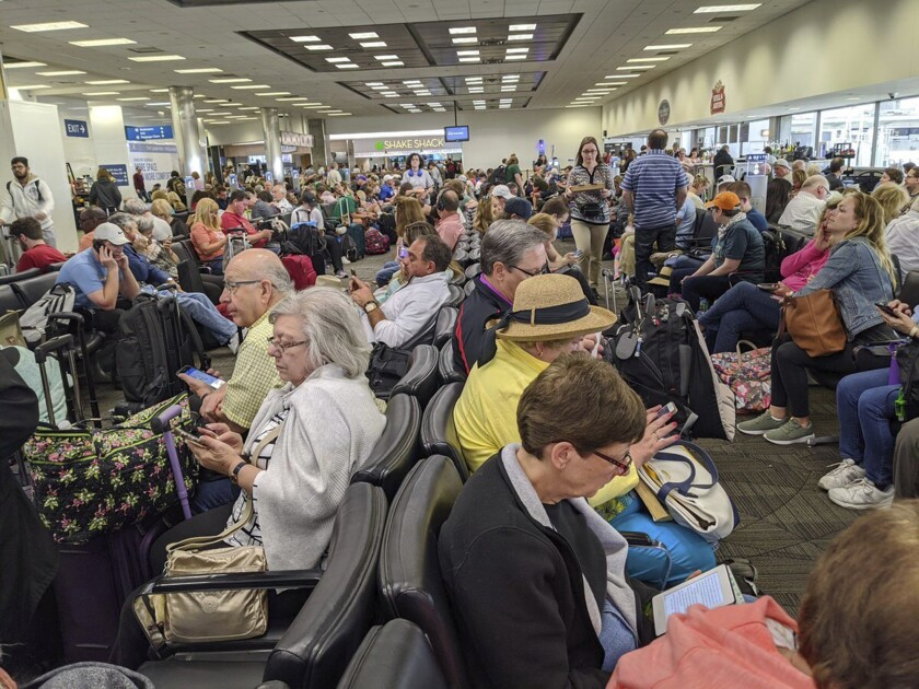 A gate area at Fort Lauderdale-Hollywood International Airport is crowded with travelers.