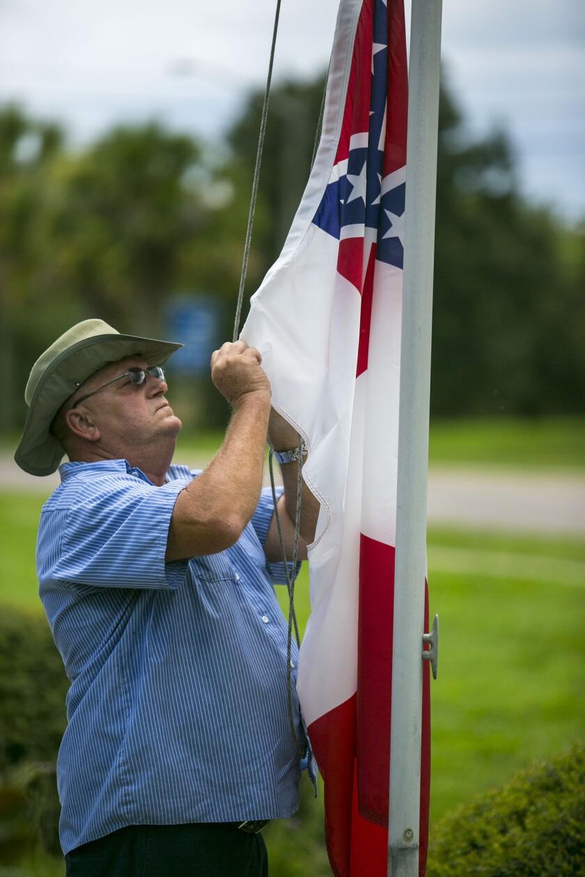 Vic Pollock, trabajador de mantenimiento del condado Marion, ata la bandera confederada a un asta afuera del Complejo Gubernamental McPherson, en Ocala, Florida, el martes 7 de julio de 2015. (Foto de Alan Youngblood/Ocala Star-Banner vía AP)