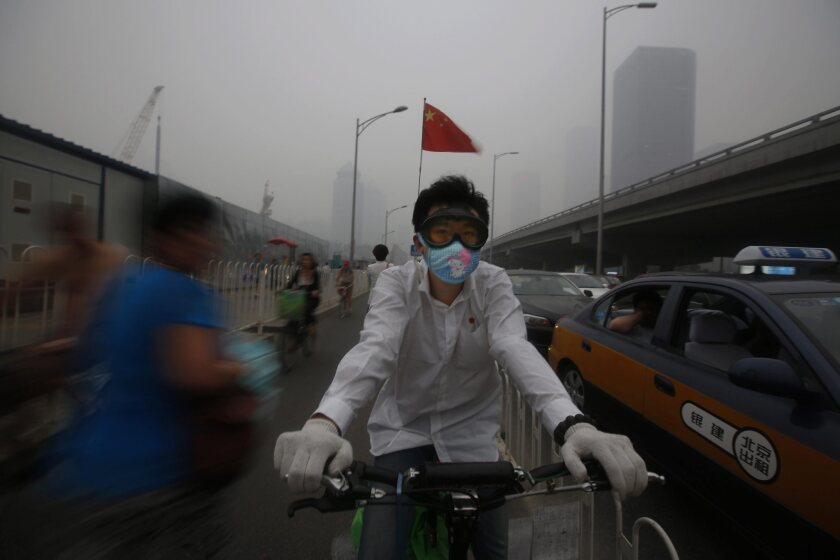 A man wears a mask while cycling in Bejing as smog engulfs the city last month.