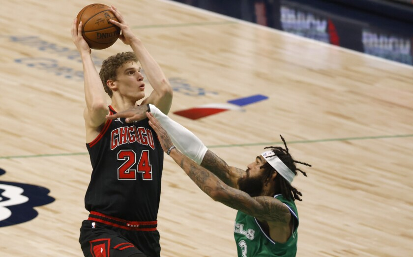 Chicago Bulls forward Lauri Markkanen (24) shoots over Dallas Mavericks center Willie Cauley-Stein (33) during the first half of an NBA basketball game, Sunday, Jan. 17, 2021, in Dallas. (AP Photo/Ron Jenkins)